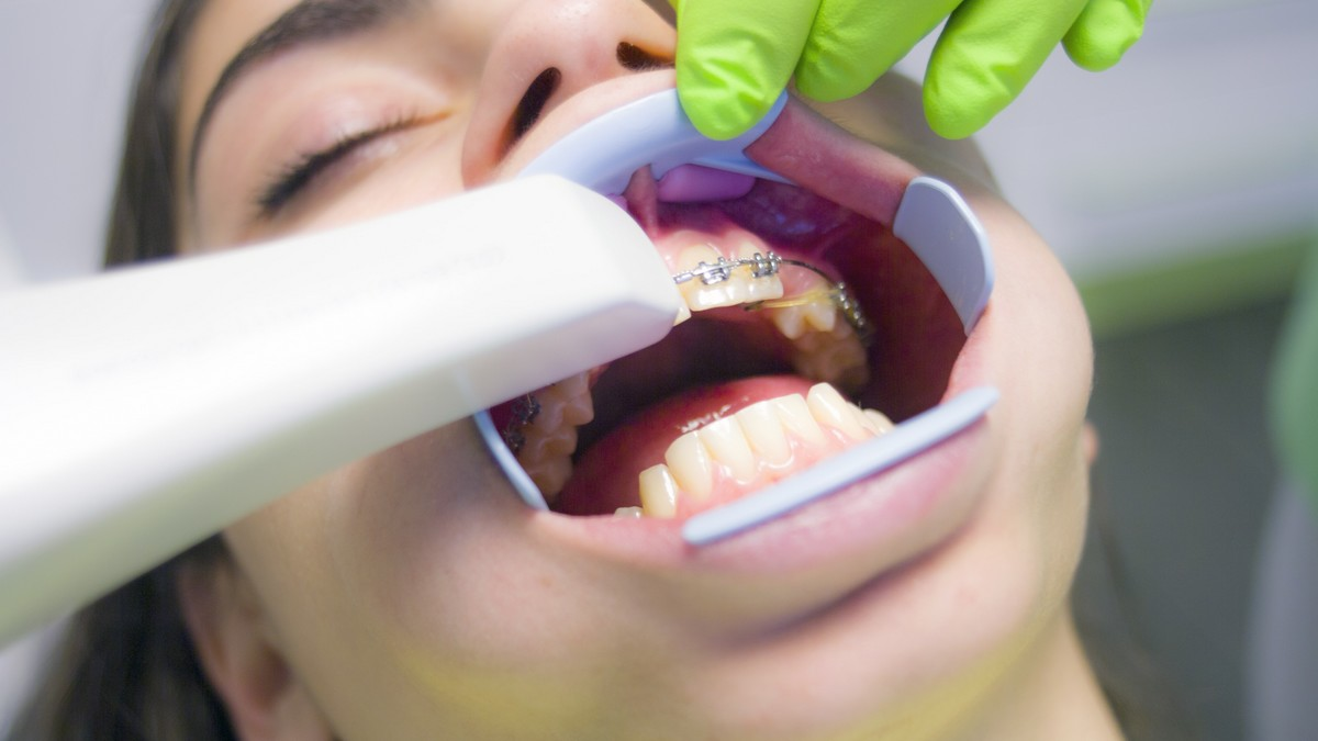 Mladá dívka je u zubaře a ten jí učí, jak vypadá správná péče o chrup.