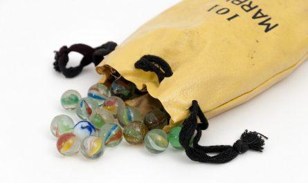 Skleněné kuličky uložené v koženém vaku.