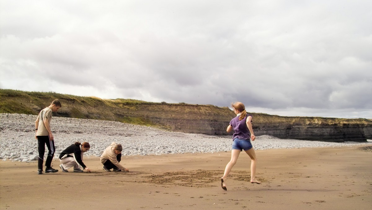 Děti na pláži se připravují na skákání panáka.